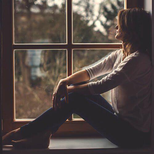 Cô gái mới chia tay người yêu ngồi buồn nhìn ra cửa sổ